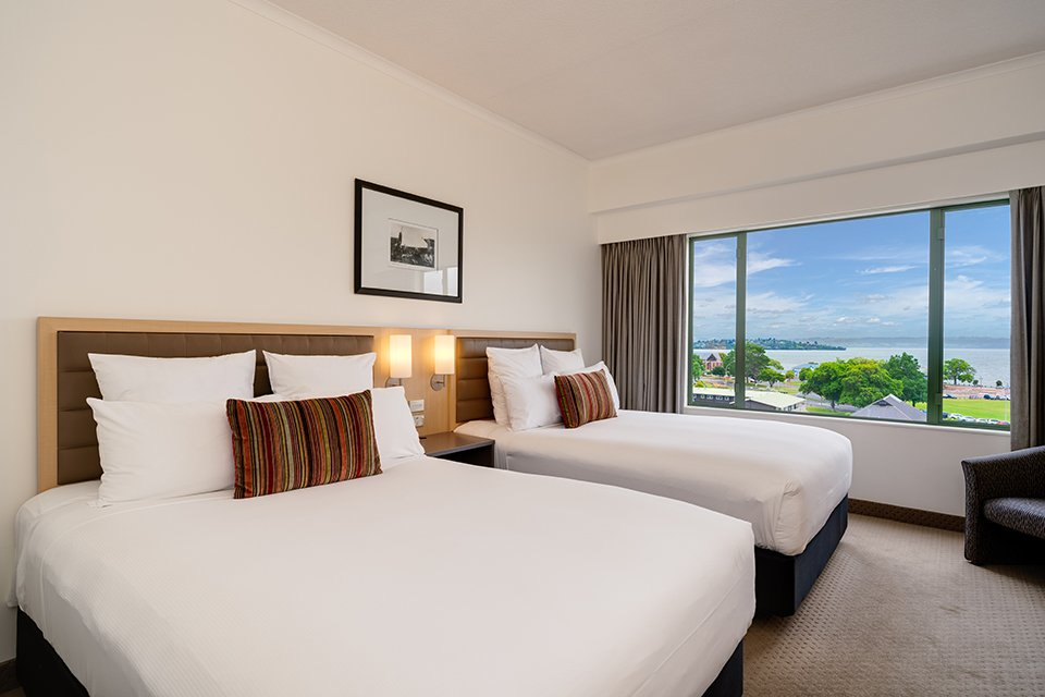 Hotel room with two queen size beds and a view of the city or lake from the window.