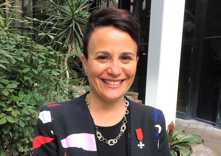 Paula Tesoriero dressed in a black suit jacket, with her MNZM award ribbon on her lapel.