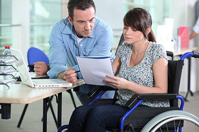 A lady in a wheelchair talking over a document with a man leaning on a table